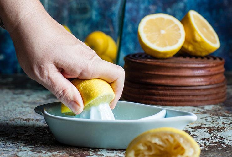 Hand squeezing lemons making lemonade